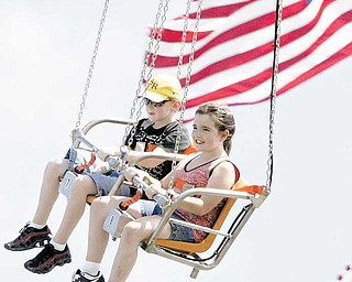 Nick Fromel, 9, of Greenford and Jamie Andrews, 10, of Austintown enjoy riding Vertigo, a swing ride that debuted Wednesday at the Canfield Fair.
