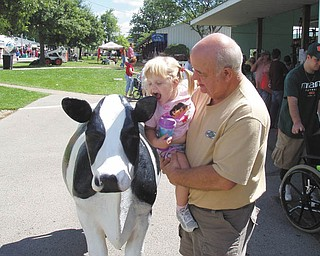 Lindsey, of Detroit, Mich., and Fred of Struthers visit the cow statue by the milking booth. Photo submitted by Danielle Springer of Detroit, Mich.