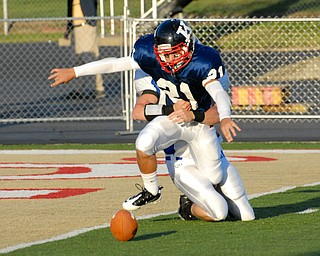 Warren JFK punter #21 Mark Fordeley and Hubbard rusher #9 Taylor Karabin battle for the loose ball after the snap went over Fordeley's head. The ball would be kicked out of the back of the endzone by a JFK player for the saftey.