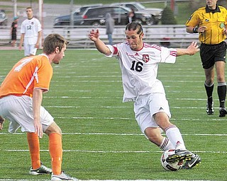 Canfield's Patrick Stickle (16) tries to maneuver around Howland's Scott Heinemann (7) during a soccer game Thursday in Canfield. The Cardinals defeated the Tigers, 3-0, with Stickle scoring two goals.