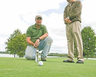 """Mike Ferranti, right, golf pro at The Lake Club in Poland, watches Thursday as course superintendent Chris Brown uses a stimpmeter to check the roll on a green. The two have spent the past several weeks making sure every blade of grass and every grain of sand on the course is up to par for the championship round of the """"Greatest Golfer of the Valley"""" tournament on Sept. 18. Opening play is Saturday at Mill Creek and Sunday at Trumbull Country Club."""