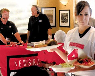 Sarah Kotch of Jackson-Milton delivers food as Eric Wolford, YSU's head football coach, left, speaks with Bob Hannon, president of United Way of Youngstown and the Mahoning Valley, while on the radio during the Score a Touchdown for the United Way event at O'Charley's in Boardman on Thursday.