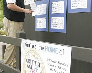 William D. Lewis| The Vindicator  Dennis Miller, golf director at Mill Creek, puts scores up at Greatest Golfer of the Valley tourney Saturday.