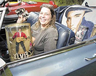 Tracy Miller of Liberty shows off Elvis memorabilia while sitting in the 1968 Cadillac DeVille she was showing at the festival in Church Hill Park in Liberty on Sunday. The event included music, food and a car show.