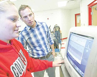 Jayson Yeagley, right, a Columbiana High School teacher and student Abby Hertel work on  a computer used in the school's video laboratory.