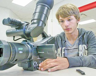 Jeff Schallick, a junior at Columbiana High School, reviews video on a video camera in the school's video lab.