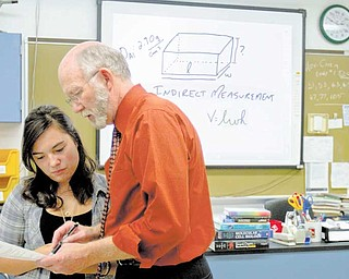 Chemistry teacher William Snyder helps junior Desiree Zepeda with a question during chemistry class at Poland Seminary High School. The instructional drawing projected in the background was created with one of the SMART Boards found in all fi ve of the high school's science labs.