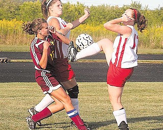 Alyssa Schauer, right, of Columbiana, attempts to kick the ball, as teammate Carolyn Gallo, center, and Katelin Smith (15) of South Range battle for position during Wednesday's soccer match in Columbiana. South Range won 3-0.