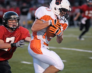 Howland WR Matt Hayes slips the tackle of Canfield's (7) Mike Ross after a short reception during their game on Friday. Photo/Mark Stahl