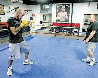 Kelly Pavlik shadowboxes in the ring as his trainer, Jack Loew, looks on Wednesday at the Southside Boxing Club.