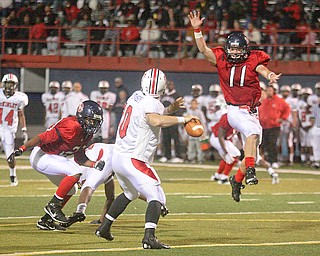 FITCH - Quarterback (10) Kyle Ohradzansky tries to elude (11) Shane Stevens and (20) Antoine Cox during their game Friday night in Austintown. - Special to The Vindicator/Nick Mays