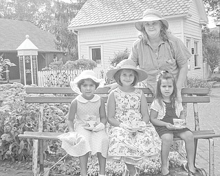 """These """"pretend pioneers"""" enjoy tea time in the garden at Western Reserve Village, a historical site where the Holborn Herb Growers Guild hosts its annual tea party. The girls, from left to right, are Sheryln Michele Himes, Annabelle Morgan Himes and Katie Koulianos, and in back is Lois Martin-Uscionowski."""