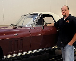 The Vindicator: Sara C. Tobias Manager Rich Seaman poses with one of his personal favorite cars, a 1966 Corvette. The Corvette, along with many of the cars in the museum was restored by employee Bob Darney, who previously worked for GM for 30 years before joining TP Tools.