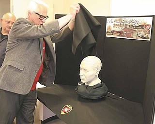 Dr. Humphrey D. Germaniuk and Bazetta Detective Joe Sofchek unveil a sculpture done by the FBI of a bust of a man whose body was found near Mosquito Lake in 2006. Call Bazetta police at 330-638-5503 if you have any information on the man.