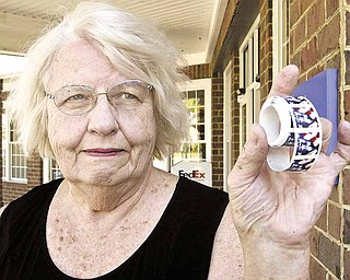 Susan McAfee of Poland Township shows a roll of stamps she found outside the Poland post office. She returned them Tuesday.