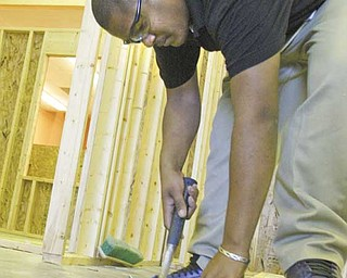 Laquail Brooks, a junior and a student in the construction technology program at Choffin Career and Technical Center, hammers in nails on the frame of a house for Habitat for Humanity of Mahoning County.