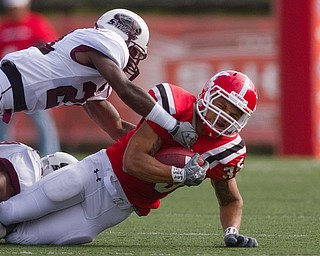 Geoffrey Hauschild|The Vindicator.Southern Illinois' Korey Lindsy (21) and an unidentifiable teamate bring down Youngstown State University's Jamaine Cook (35) during the first quarter of a game at Youngstown State University's Stambaugh Stadium on Saturday afternoon.