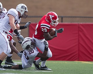 Geoffrey Hauschild|The Vindicator.Southern Illinois' Terrell Wilson (20) brings down Youngstown State University's Dominique Barnes (29) during the first quarter of a game at Youngstown State University's Stambaugh Stadium on Saturday afternoon.