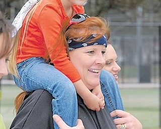 Danielle Houshton crosses the finish line with Emma Ames on her shoulders during Sunday morning's 19th annual MS Super Walk that began in Mill Creek MetroParks' James L. Wick Recreation Area.
