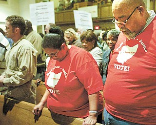 Among those praying at Monday night's Community Congress at Trinity United Methodist Church downtown were Gladys Bowers and Thomas Swanson, attending with a group from Union Baptist Church.