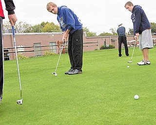 Geoffrey Hauschild|The Vindicator.McDonald High School golf team members' Zach Gillespie, Jason White, and Brandon Pustay practice their putting at the Mahoning Country Club during a practice tuesday evenning..