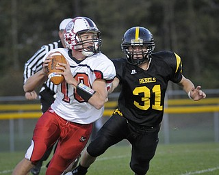 Columbiana QB Austin Barbato (10) eludes the tackel of Crestview's Tom Oliver (31) during their game at Crestview on Friday night. Photo/Mark Stahl