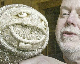 """James S. Rodgers Jr., a Youngstown-based ceramic and pottery artist, shows an example of his work during the """"Artists by the River"""" fundraiser Sunday sponsored by the Altrusa Club of Youngstown. Proceeds will benefit the clubs's Plant the Seed to Read event next March 26."""