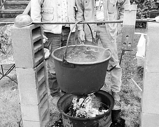 A fire was kept burning beneath a huge copper kettle all day on Sept. 25 by members of the Salem Historical Society as they demonstrated how settlers once made apple butter in the outdoors. Among those cooking breakfast, soup and coffee over the open fire while helping to produce 40 jars of fresh apple butter were John Gilbert, left, and Tim Burkey. This year's batch included apples harvested from a tree in the Historical Society's garden. The apple butter will be sold in pint and half pint jars by the society at 208 S. Broadway Ave., Salem. For additional information call 330-337-8514 or 330-332-0129.