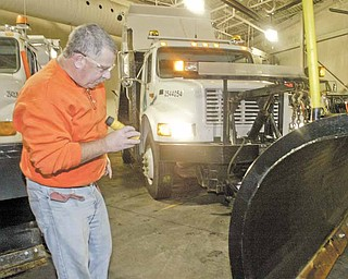 """Rick Sause, an employee with the Ohio Department of Transporation, inspects a snowplow Wednesday during an annual preseason inspection. ODOT District 4, which encompasses Mahoning, Trumbull, Ashtabula, Portage, Summit and Stark counties, had a """"dry run"""" Wednesday morning and tested equipment for winter weather at its Canfield garage."""