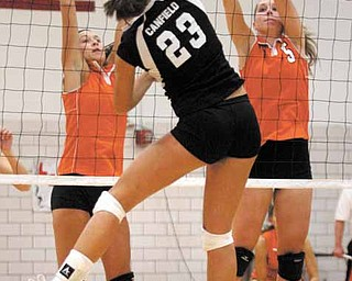 VOLLEYBALL - (23) Hannah Milstead of Canfield spikes the ball as (7) Katie Kennedy and (5) Larissa Santangelo go for the block Monday night. - Special to The Vindicator/Nick Mays