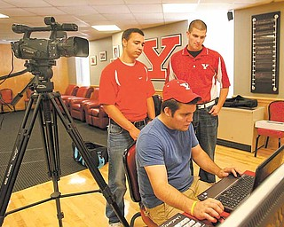 YSU students Zack Humphries, back left, and Pat Andrews, back right, are the anchors for Penguin Rundown, a weekly highlights show on Penguin athletics. Humphries is an Ursuline High graduate, while Andrews graduated from Canfield High School. Jon Raidel, seated, is the executive producer. He is a graduate of Girard High School.