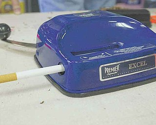 Cheap Tobacco specializes in roll-your-own cigarette products and tools like this manual-rolling machine. Rising cigarette prices, and the economic downturn, have driven many smokers to roll their own cigarettes.  .
