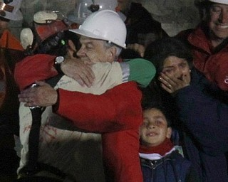 Chile's President Sebastian Pinera embraces miner Florencio Antonio Avalos Silva after he was rescued from the collapsed San Jose gold and copper mine where he was trapped with 32 other miners for over two months near Copiapo, Chile, Tuesday Oct. 12, 2010. at the San Jose Mine near Copiapo, Chile Wednesday, Oct. 13, 2010. Next to Pinera Avalos wife and daughter.(AP Photo/Roberto Candia)