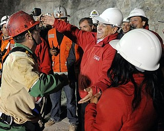 In this photo released by the Chilean presidential press office, Chile's President Sebastian Pinera, fifth right, open his arms to hug rescued miner Mario Sepulveda,after Sepulveda was rescued from the collapsed San Jose gold and copper mine where he was trapped with 32 other miners for over two months near Copiapo, Chile, early Wednesday Oct. 13, 2010.  (AP Photo/Jose Manuel de la Maza, Chilean presidential press office)