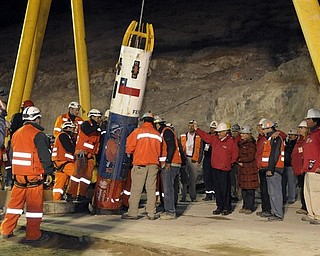 In this photo released by the Chilean presidential press office, Chile's President Sebastian Pinera, center right in red jacket, waves to rescue worker Manuel Gonzalez Paves as he is lowered into the mine in the capsule to begin the rescue of 33 trapped miners at the San Jose Mine near Copiapo, Chile, Tuesday Oct. 12, 2010. The first of 33 trapped miners is expected to be lifted to the surface late Tuesday after surviving more than two months below ground. (AP Photo/Alex Ibanez, Chilean presidential press office)
