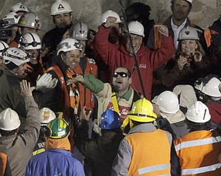 Chile's President Sebastian Pinera, center top, cheers as rescued miner Mario Sepulveda Espina, center, salutes after  being rescued from the the collapsed San Jose gold and copper mine where he was trapped with 32 other miners for over two months near Copiapo, Chile, early Wednesday Oct. 13, 2010.(AP Photo/Jorge Saenz)
