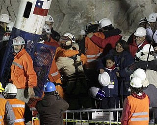 Rescued miner Florencio Antonio Avalos Silva embarces one of the rescue workers as his wife Monica and son Byron, center right,  look on next to President Sebastian Pinera, second from right,  after he arrived to the surface from the collapsed San Jose gold and copper mine where he was trapped with 32 other miners for over two months near Copiapo, Chile,  early Wednesday, Oct. 13, 2010.(AP Photo/Jorge Saenz)