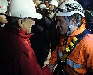 In this photo released by the Chilean presidential press office, Chile's President Sebastian Pinera, left, shakes hands with rescuer Manuel Gonzalez before he's lowered into the mine where miners are trapped to begin their rescue at the San Jose mine, near Copiapo, Chile, Tuesday, Oct. 12, 2010. (AP Photo/Alex Ibanez, Chilean presidential press office)