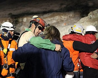In this photo released by the Chilean government, miner Florencio Avalos, second left, hugs a relative after he was rescued from the collapsed San Jose gold and copper mine where he was trapped with 32 other miners for over two months near Copiapo, Chile, early Wednesday, Oct. 13, 2010. (AP Photo/Hugo Infante, Chilean government)
