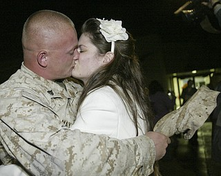 William D. Lewis|The Vindicator Marine Reservist Cory May kisses his wife Torrie May upon arriving at the Youngstown Airbase  from Afghanistan Thursday night. They are from Cambridge, OH.