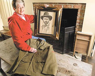 Colette Chuey displays a print of Ulysses S. Grant as she holds the jacket of an authentic World War I uniform at the Barnhisel House in Girard. The Girard Historical Society is having a Cemetery Walk to raise money for the upkeep of the house, which is a museum that features antiques from the 1800s.