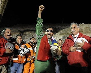 In this photo released by the Chilean Presidential Press Office, the last miner to be rescued, Luis Urzua, center, gestures as Chile's President Sebastian Pinera, right, looks on after his rescue from the collapsed San Jose gold and copper mine where he had been trapped with 32 other miners for over two months near Copiapo, Chile, Wednesday Oct. 13, 2010.  The 69-day underground ordeal reached its end Wednesday night after 33 trapped miners were hauled up in a cage through a narrow hole drilled through 2,000 feet of rock.  (AP Photo/Alex Ibanez, Chilean Presidential Press Office)