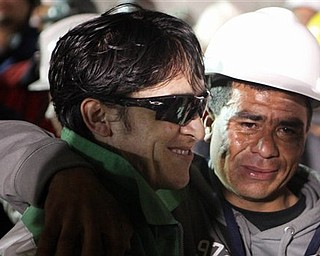 In this photo released by the Chilean government, miner Ariel Ticona Yanez, left, smiles after being pulled out of the San Jose gold and copper mine where he had been trapped with 32 other miners for over two months near Copiapo, Chile, Wednesday Oct. 13, 2010.  (AP Photo/Chilean Government, Hugo Infante)