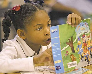 Dawn Ferguson, a second-grader at Legacy Academy, reads during the World Series of Reading event.  YSU baseball players participated Wednesday.