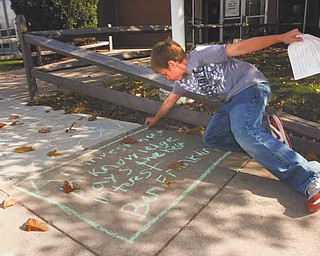 Fifth-grader Tyler Heitman outlines a quote by Benjamin Franklin on the sidewalk outside Frank Ohl Intermediate School, Austintown. Tyler was one of 400 fifth-graders at the school who participated Wednesday in National Day on Writing by chalking their favorite quotes.