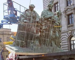 Geoffrey Hauschild|The Vindicator.Construction workers work to remove the 3 figure statue from the top of the Mahoning County Courthouse in order to perform repairs on the deteriorating pedestal that supports them.