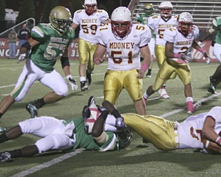 ROBERT K. YOSAY | THE VINDICATOR..Brought down behind the line  Mooney #5   Kevin McGuire QB is caught behind the line by #1  Trevor Smith - Ursuline vs Mooney at YSU stadium ...  --30-..