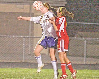 (20) Megan Harkins of Champion gets a face full of ball as (13) Andrea Ryhal plays defense during their game Monday night.