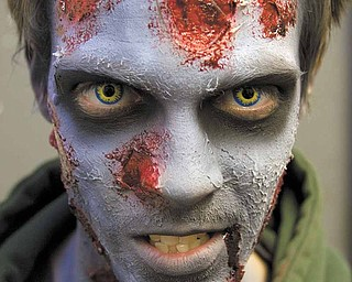 Josh Hamilton, of Salem, in preparation for his zombie character who weilds a chainsaw at the Canfield Scaregrounds on Thursday evening.