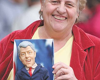 Sue Watson of Rogers shows off her dancing-and-singing Bill Clinton doll as she waits outside the Mahoning County Democratic Party headquarters in Youngstown for free tickets to a Saturday breakfast gathering with the former president.